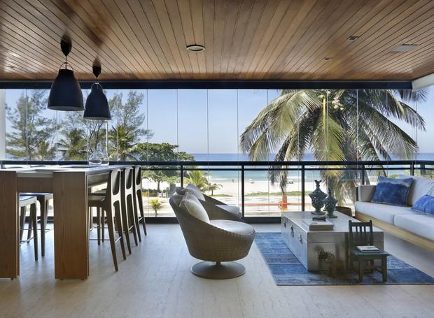 Na varanda, a vista para a praia da Barra da Tijuca, no Rio de Janeiro, é o espaço mais disputado do apartamento. O forro de madeira no teto deixa o ambiente mais acolhedor (Foto: Denilson Machado, MCA Estúdio/Divulgação)