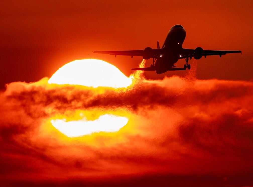 Um avião decola durante o amanhecer no aeroporto internacional de Frankfurt, na Alemanha — Foto: Michael Probst/AP