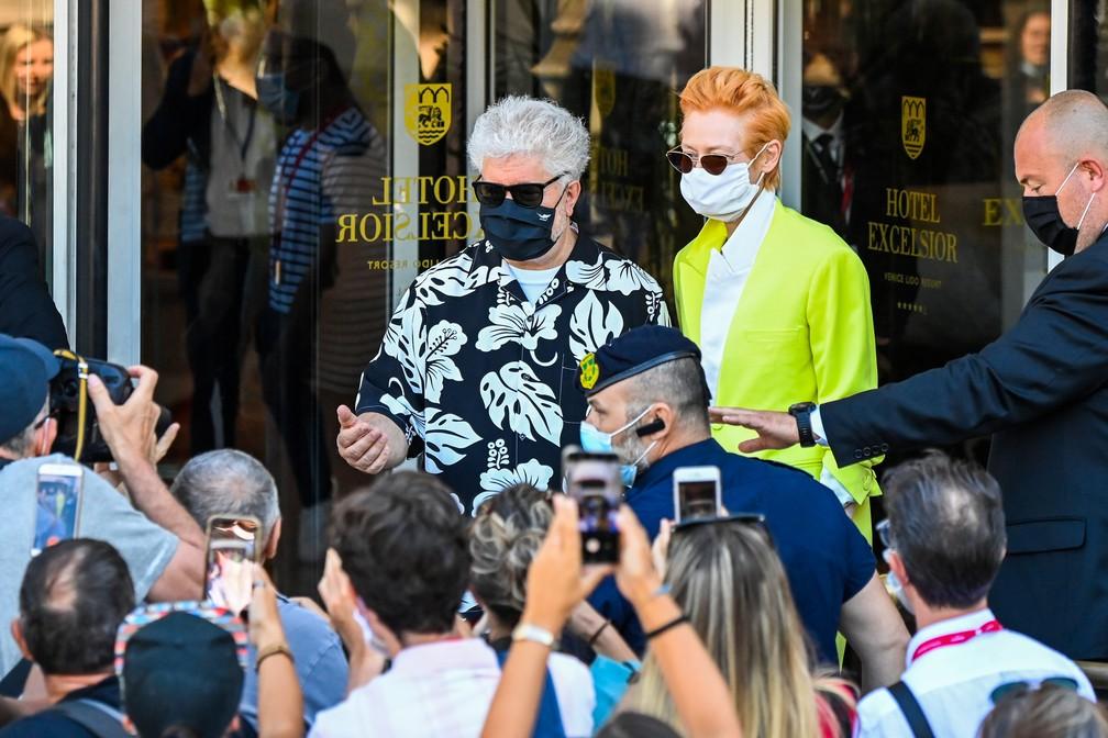 O diretor espanhol Pedro Almodovar e a atriz britânica Tilda Swinton encontram fãs e fotógrafos ao deixarem hotel em direção ao festival — Foto: ALBERTO PIZZOLI / AFP