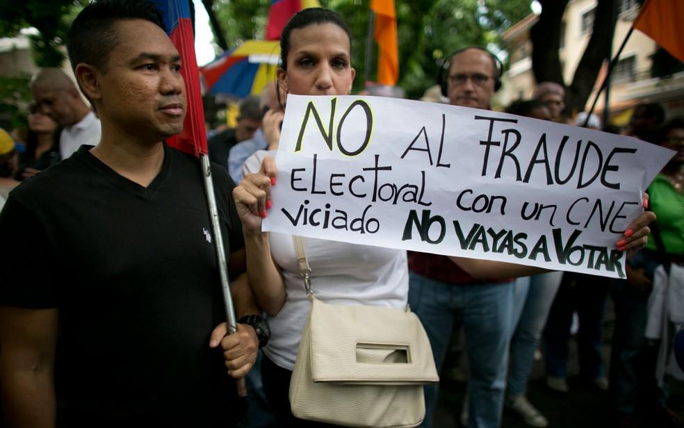 Mulher carrega um cartaz com a mensagem 'Não à fraude eleitoral com um Conselho Eleitoral Nacional viciado. Não vote' durante protesto contra as eleições presidenciais em Caracas, na Venezuela, na quarta-feira (16) — Foto: AP Photo/Ariana Cubillos