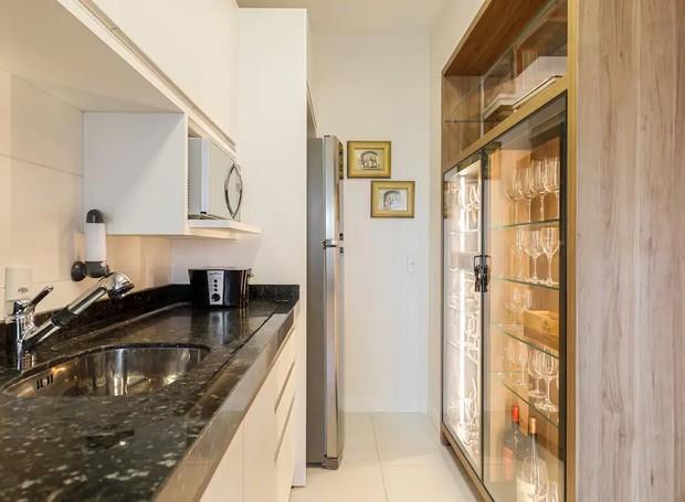 A marcenaria também serve de divisória entre a cozinha e a sala. Ali, um armário com portas de vidro exibe as taças finas (Foto: Airbnb/ Reprodução)