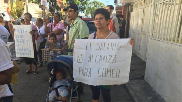 Venezuelanos protestam por conta da pobreza no país com cartazes dizendo que o salário não lhes permite comer e que não há luz, água e/ou gás (Foto: GUILLERMO OLMO / BBC MUNDO)