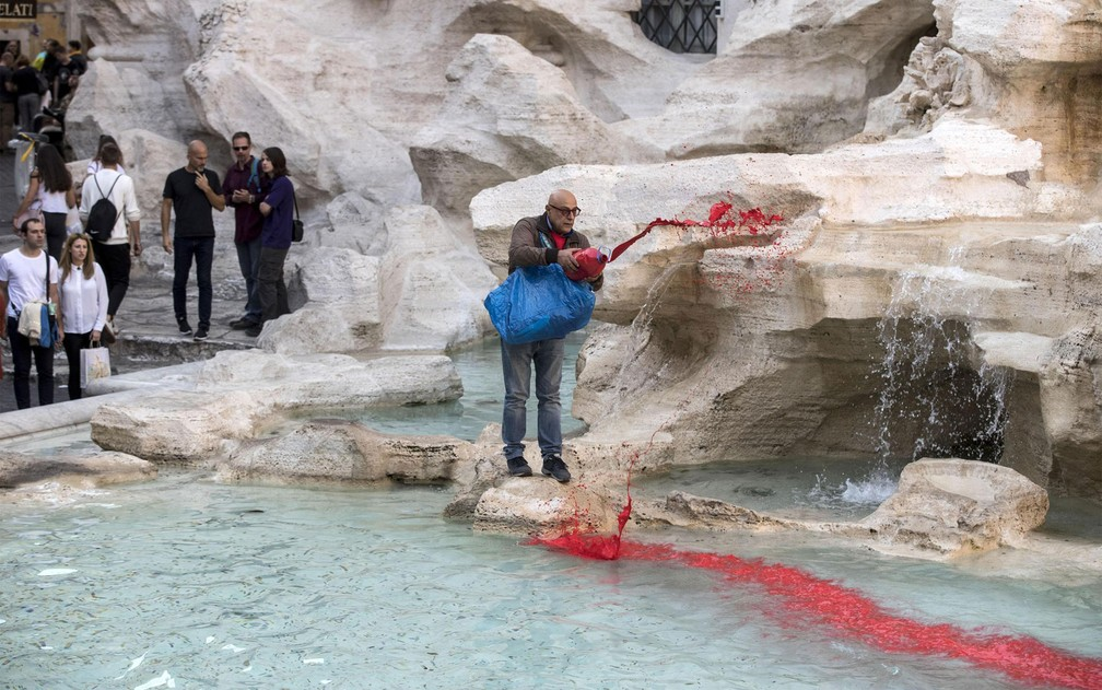 Graziano Cecchini despeja tinta vermelha nas águas da Fontana di Trevi, em Roma, na quinta-Feira (26) (Foto: Massimo Percossi/ANSA via AP)