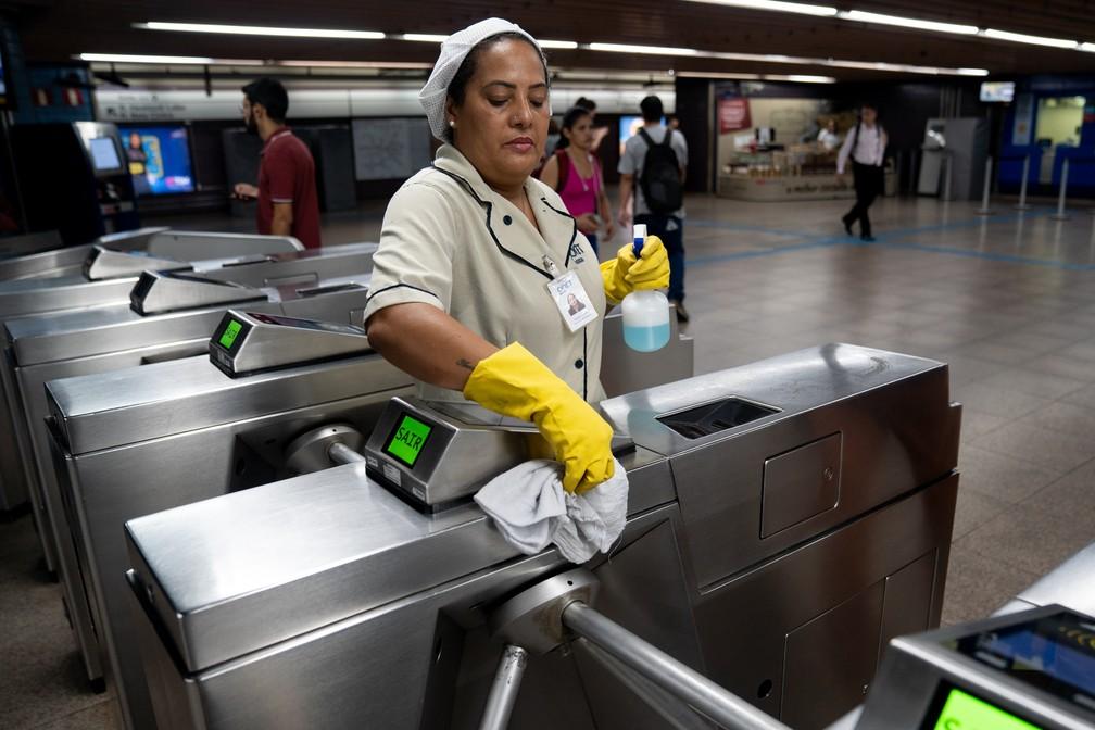 16 de março - Funcionária do metrô limpa catracas na estação Consolação da linha 2-verde do metrô de São Paulo. A higienização de trens e estações foi intensificada a partir desta semana devido a epidemia do novo coronavírus  — Foto: Marcelo Brandt/G1