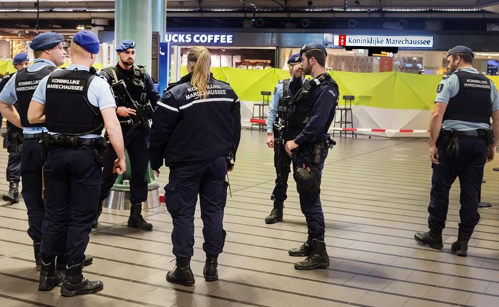 Policiais se reúnem no aeroporto  Schiphol, em Amsterdam, após homem armado com faca ser baleado e detido (Foto: Evert Elzinga / ANP / AFP)