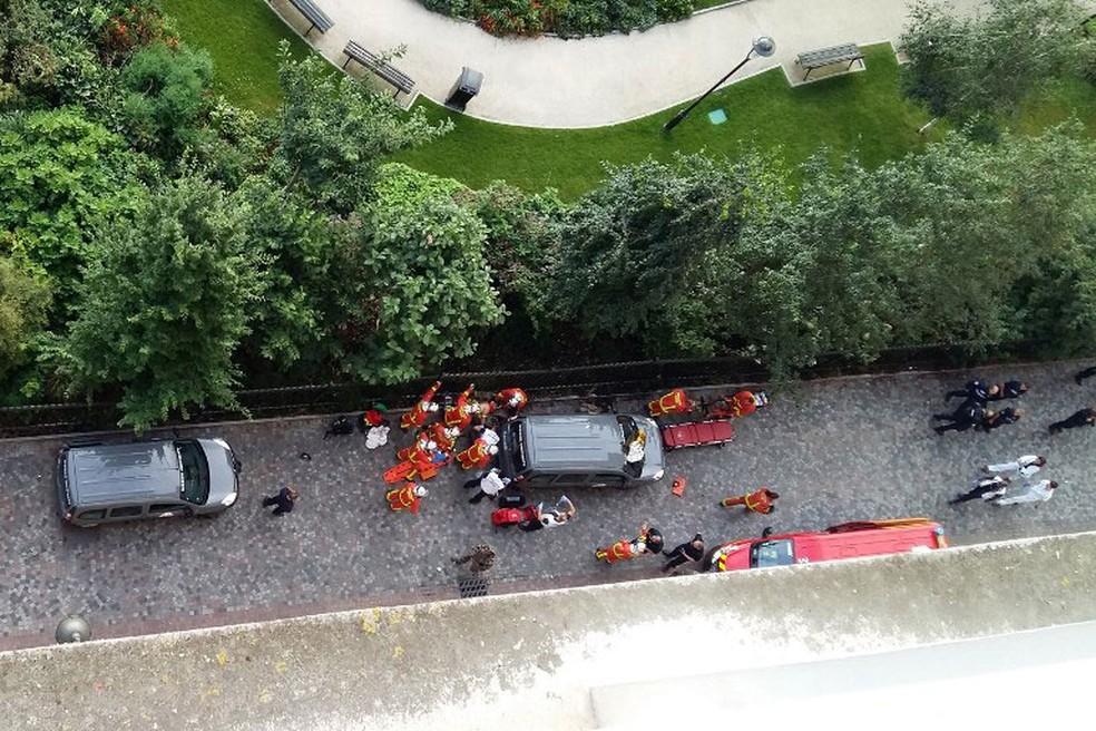 Policiais e funcionários do serviço de resgate se aproximam do local onde agentes da polícia antiterrorista foram atropelados, em Levallois-Perret, na França, nesta quarta-feira (9)  (Foto: Thierry Chappé / AFP )