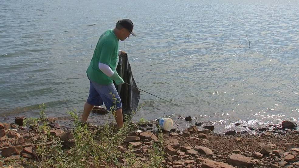 Marcos pega lixo jogado às margens do Rio Tietê — Foto: Reprodução/TV TEM