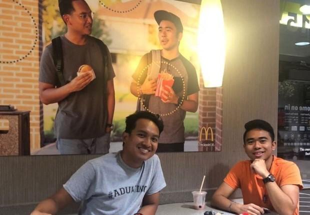 Jevh e Christian ao lado do pôster que produziram e penduraram no McDonald's (Foto: @Jevholution via BBC)