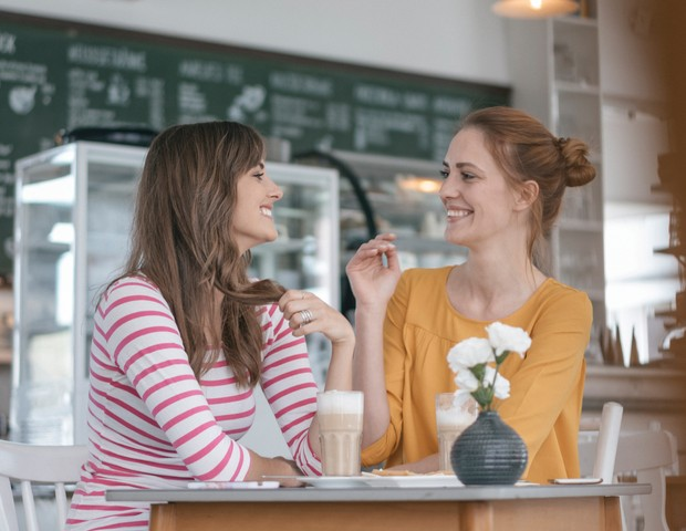 Two girlfriends meeting in a coffee shop, talking (Foto: Getty Images/Westend61)