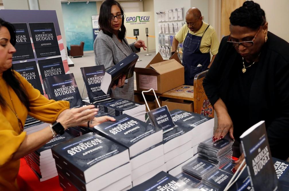 Funcionários do governo americano organização edições impressas da proposta de orçamento da Casa Branca para 2019 (Foto: Leah Millis/Reuters)