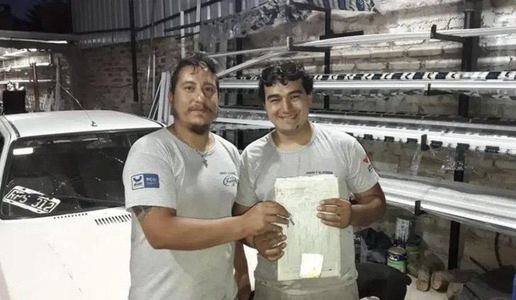 Eduardo (chefe) e Franco com a documentação do carro novo — Foto: Reprodução/ Jornal Río Negro