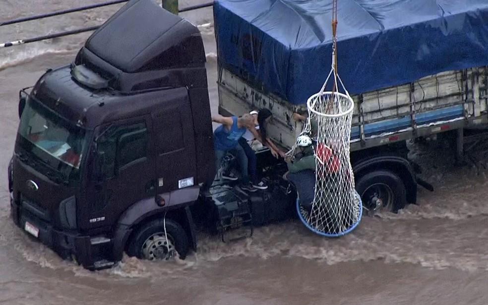 Cesto que seria içado com vítimas por helicóptero engancha em caminhão no meio de enchente — Foto: Reprodução/TV Globo