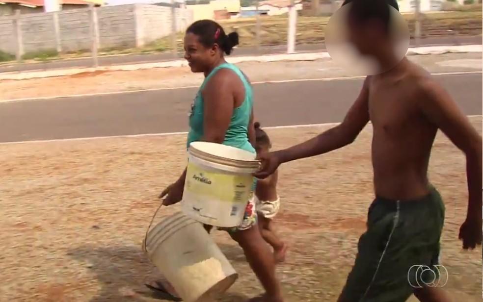 Moradores com baldes em busca de água no Residencial Buena Vista, em Goiânia, Goiás (Foto: Reprodução/TV Anhanguera)