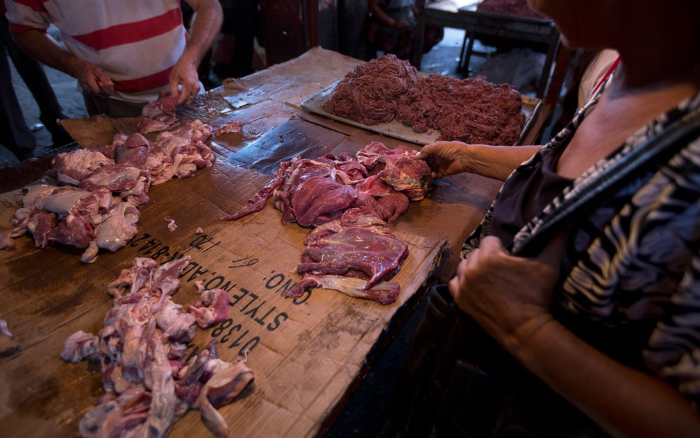 Consumidores examinam carne estragada, misturada à carne fresca, oferecida em Mercado em Maracaibo, na Venezuela, no dia 19 de agosto — Foto: AP Photo/Fernando Llano