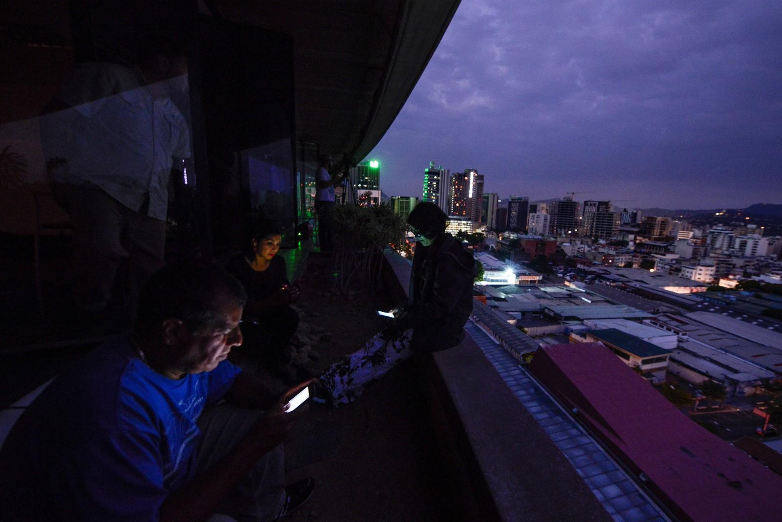 Pessoas usam celulares durante apagão em Caracas, no dia 7 de março — Foto: Matias Delacroix/AFP
