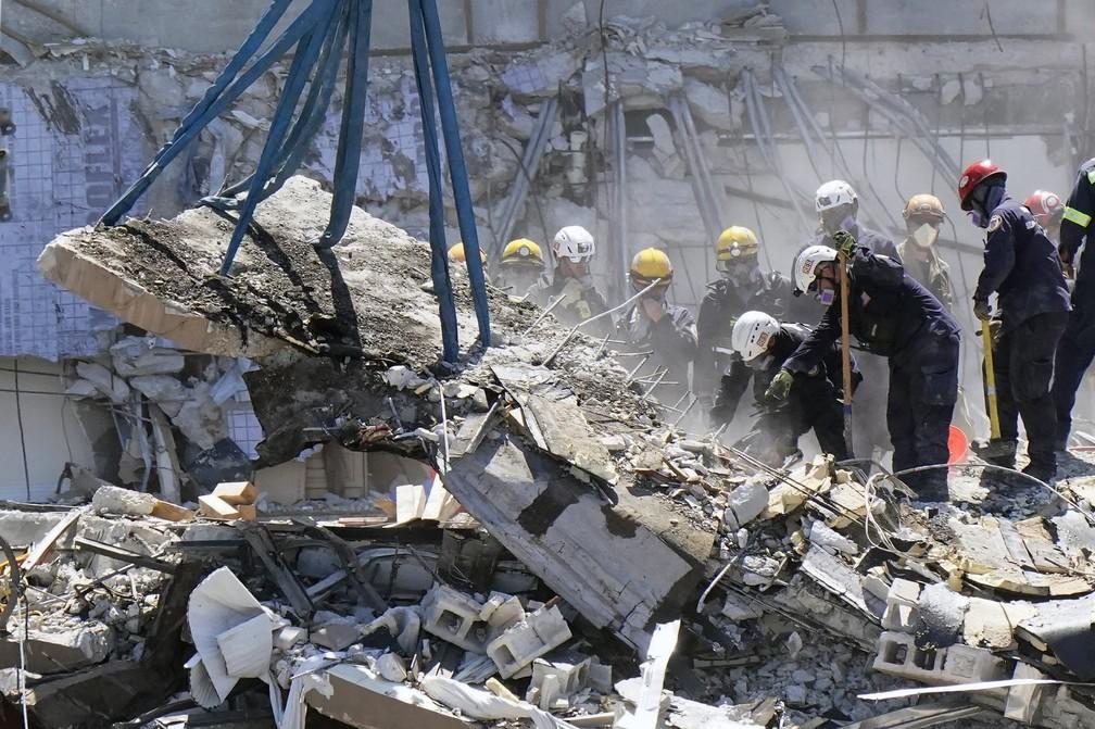 Equipes de resgate trabalham nos escombros do condomínio Champlain Towers South, em 27 de junho de 2021, em Surfside. Prédio desabou parcialmente no dia 24 na região de Miami, na Flórida, nos Estados Unidos — Foto: Wilfredo Lee/AP