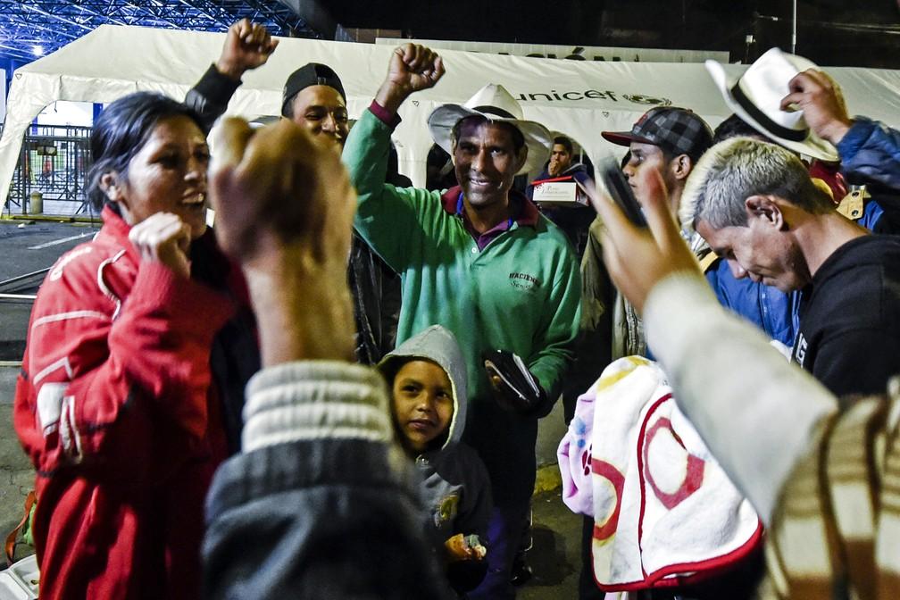 Venezuelanos comemoram depois de receber cartão que os autoriza a entrar no Equador (Foto: Luis Robayo/ AFP)