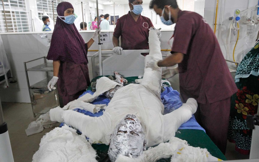 Médicos tratam de um muçulmano queimado após explosão em mesquita em Bangladesh — Foto: Abdul Goni / AP Photo