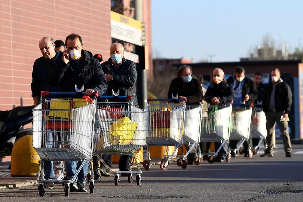 Pioltello, em Milão, pessoas usam máscara para ir ao supermercado no 2º dia da quarentena imposta a todo o país para frear o coronavírus. — Foto: REUTERS/Flavio Lo Scalzo