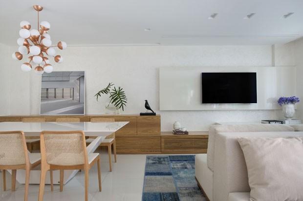 Móvel de madeira une sala de estar e jantar em apartamento jovem no Rio (Foto: Denilson Machado/ MCA Estúdio)