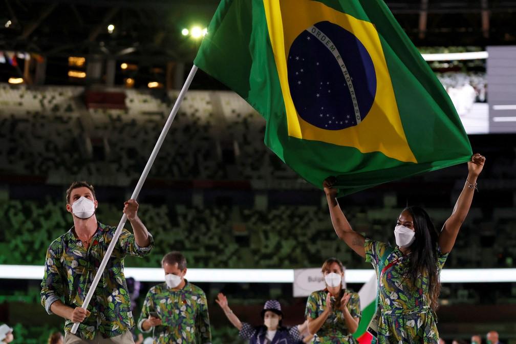 Ketleyn Quadros e Bruno Mossa carregam a bandeira do Brasil durante a cerimônia de abertura dos Jogos Olímpicos de Tóquio, no Japão — Foto: Odd Andersen/AFP