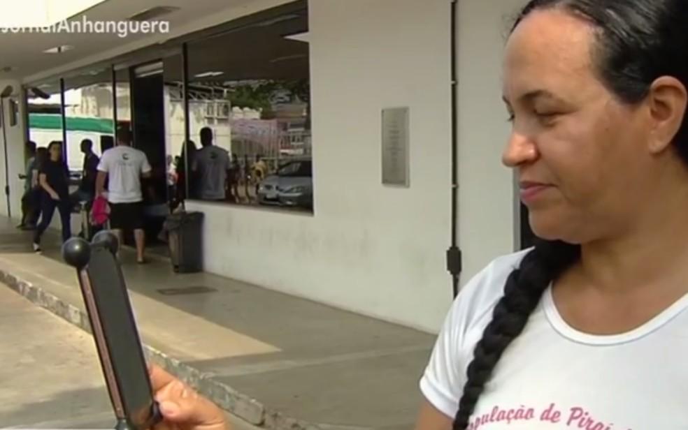 Tia que acompanha siamesas em hospital de Goiânia conversa com irmã, que está na Bahia, por telefone — Foto: Reprodução/TV Anhanguera