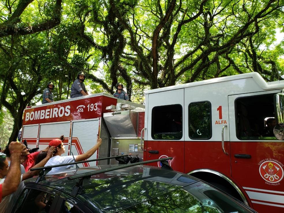 Carro dos Bombeiros chega com corpo de Gugu ao cemitério sob aplausos dos fãs — Foto: Bárbara Muniz Vieira/G1
