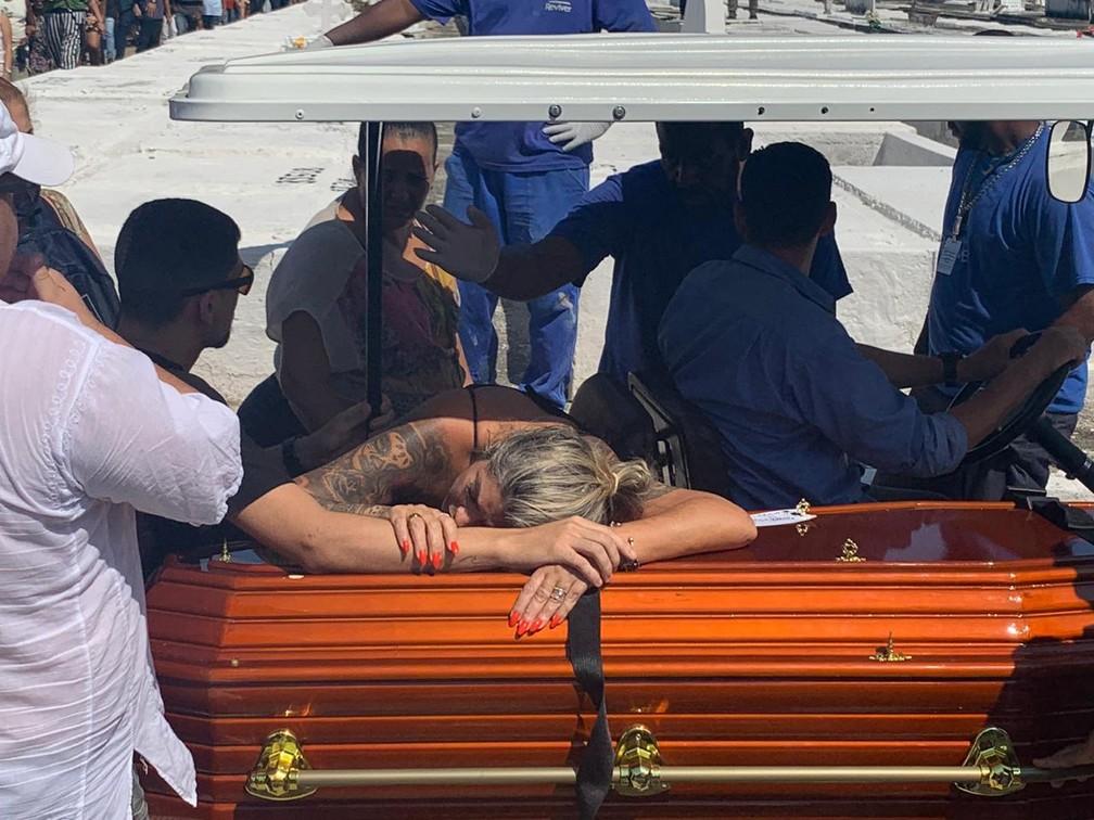Mãe abraça caixão do filho na saída para o enterro — Foto: Matheus Rodrigues/ G1 Rio