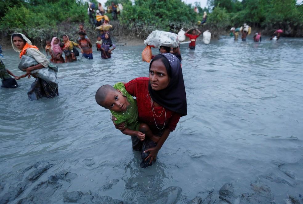 -  Mulher rohingya atravessa rio segurando seu filho na fronteira entre Myanmar e Bangladesh, perto de Cox's Bazar  Foto: Adnan Abidi/Reuters