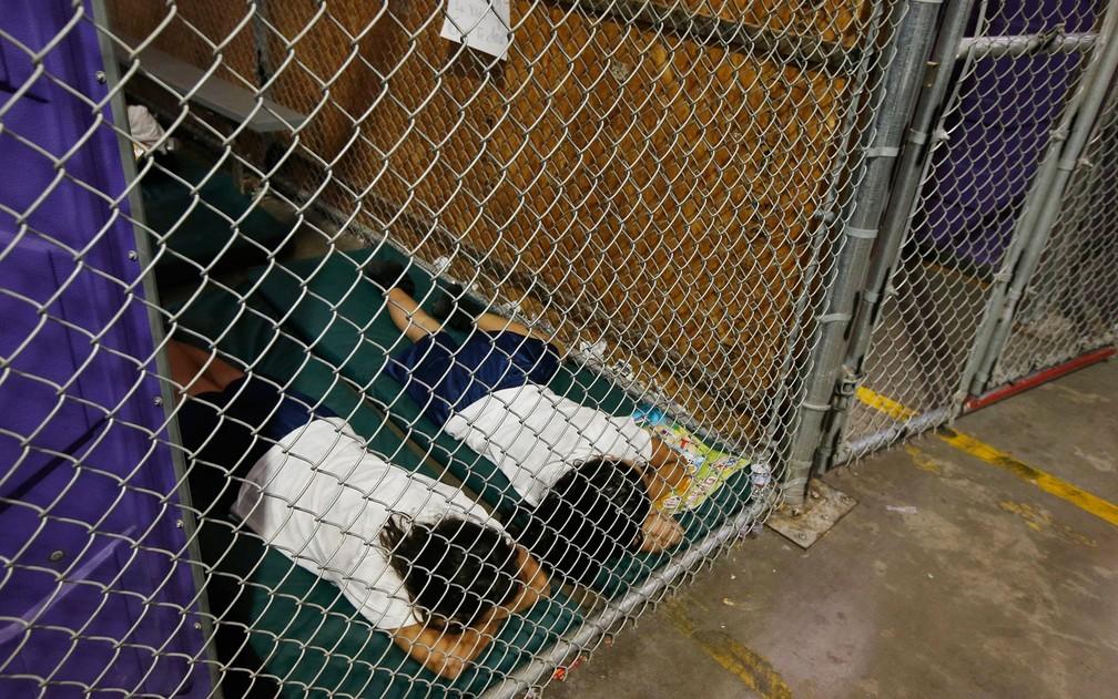 Em foto de 18 de junho de 2014, duas jovens dormem em uma cela, enquanto crianças são separadas por idade e gênero, enquanto centenas de imigrantes são registrados e mantidos no Centro de Alfândega e Colocação e Proteção de Fronteiras dos EUA, em Nogales, Arizona (Foto: AP Photo/Ross D. Franklin, Pool)