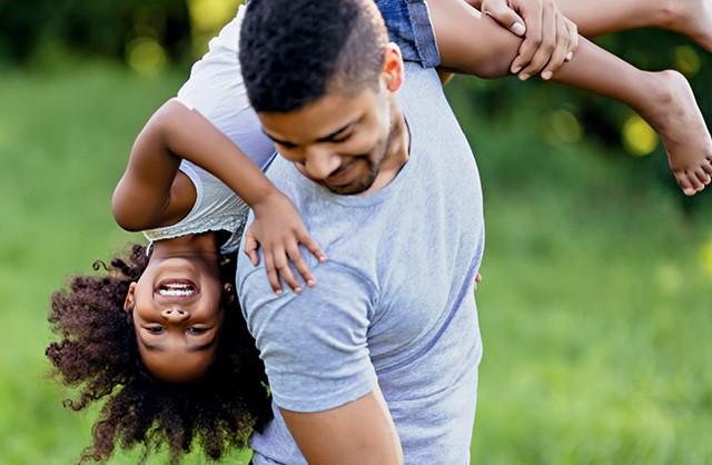 Pai e filha negros se divertem sorrindo e brincando de carregar a criança no ombro (Foto: Thinkstock)