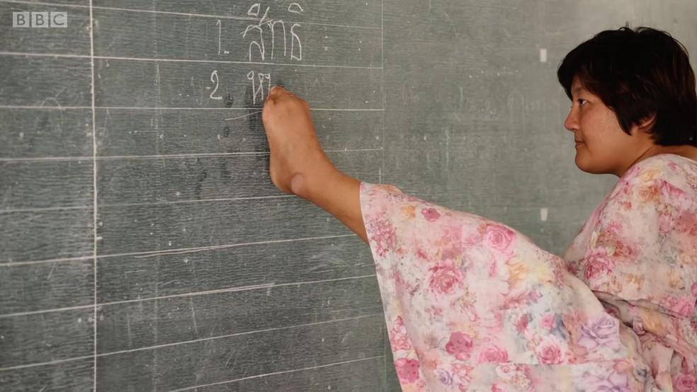 A professora tailandesa Patcharamon Sawana escreve com os pés (Foto: Reprodução BBC)