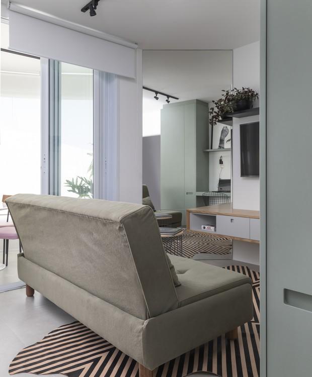 O tapete Pelle, de Maraí Valente, é a grande estrela da sala de estar. Uma parede em ângulo coberta de espelho multiplica a claridade que vem de fora e cria a impressão de espaço maior (Foto: Evelyn Müller/Divulgação )