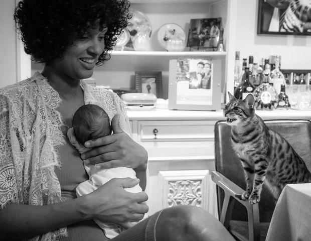 Rosângela Jacquin com um dos filhos nos braços, sendo observada pelo gato Johnny (Foto: Reprodução Instagram)
