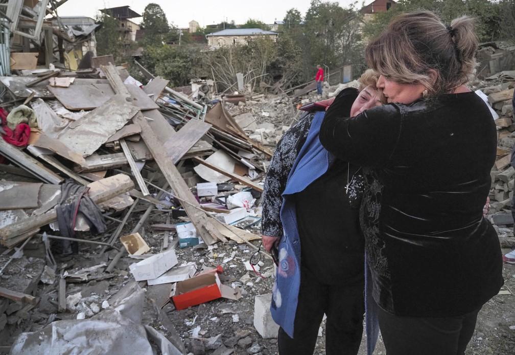 Vizinha consola mulher que teve a casa destruída durante ataque a Stepanakert, na região de Nagorno-Karabakh, neste sábado (17) — Foto: AP