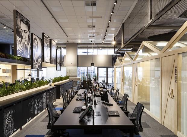 As mesas de trabalho ficam dispostas no centro do salão, ladeadas pelas salas de reunião. A solução é prática e funcional para a rotina dos analistas (Foto: Ricardo Bassetti/Divulgação)