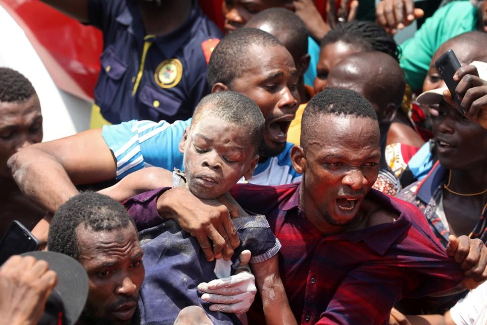 Homem carrega criança resgatada dos escombros de prédio de escola que desabou em Lagos, na Nigéria — Foto: Temilade Adelaja/Reuters
