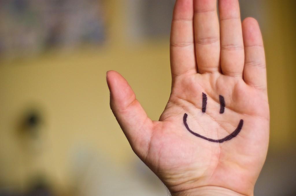 Palma da mão com um emoji feliz desenhado. (Foto: Ben Smith/Flickr)