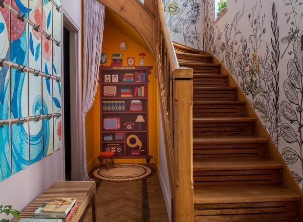"""Um """"clubinho"""" escondido embaixo da escada, no melhor estilo quartinho do Harry Potter, é o ponto de encontro de crianças de 4 a 7 anos, que poderão curtir ali um cafofo dos mais confortáveis. Autoria de Marcia Filgueiras e Paola Belfort.  (Foto: Casa Na Toca/Divulgação)"""