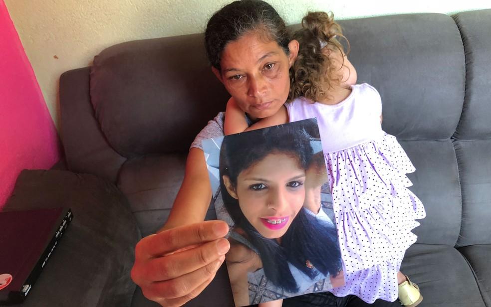 Marlene Santos segura foto da filha morta enquanto segura a neta (Foto: Kleber Tomaz/G1 )