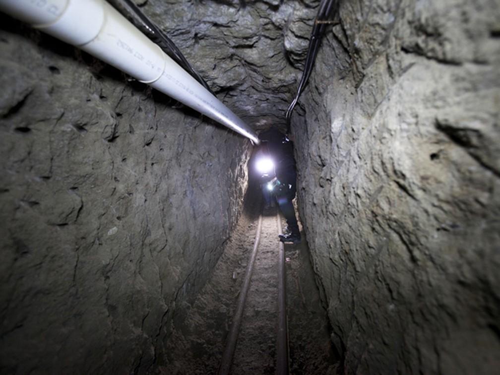 Um policial federal é visto no túnel usado por 'El Chapo' em sua fuga da prisão de segurança máxima Altiplano, em Almoloya, no México — Foto: AP Photo/Marco Ugarte