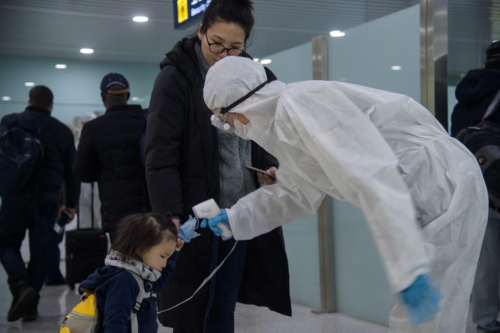 Uma criança tem sua temperatura medida enquanto diplomatas estrangeiros e funcionários da embaixada se preparam para embarcar em um voo para Vladivostok no Aeroporto Internacional de Pyongyang em 9 de março de 2020. — Foto: Kim Won Jin/AFP
