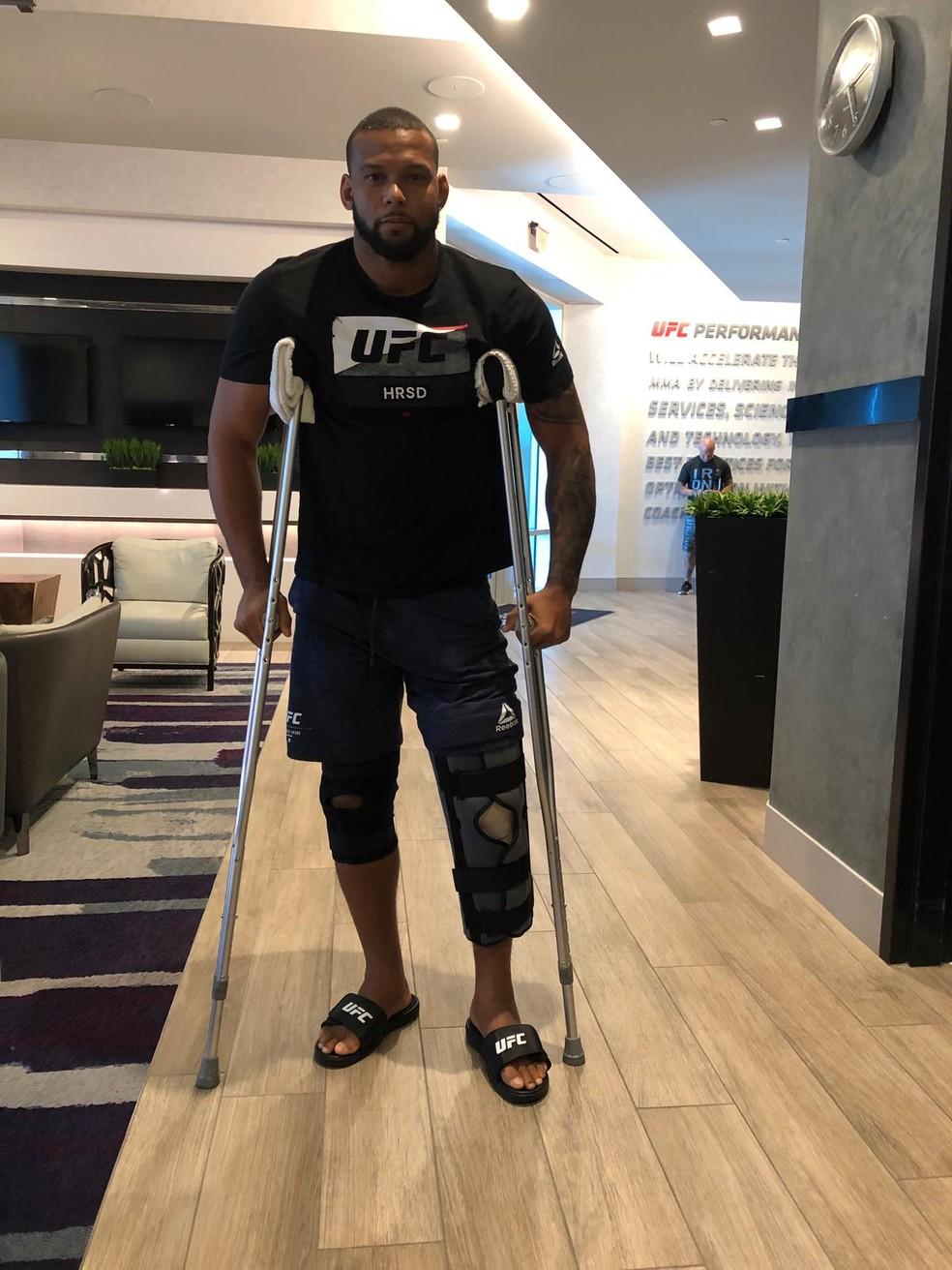 Com o joelho esquerdo imobilizado e o joelho direito protegido, Thiago Marreta se locomove de muletas enquanto aguarda cirurgia — Foto: Evelyn Rodrigues
