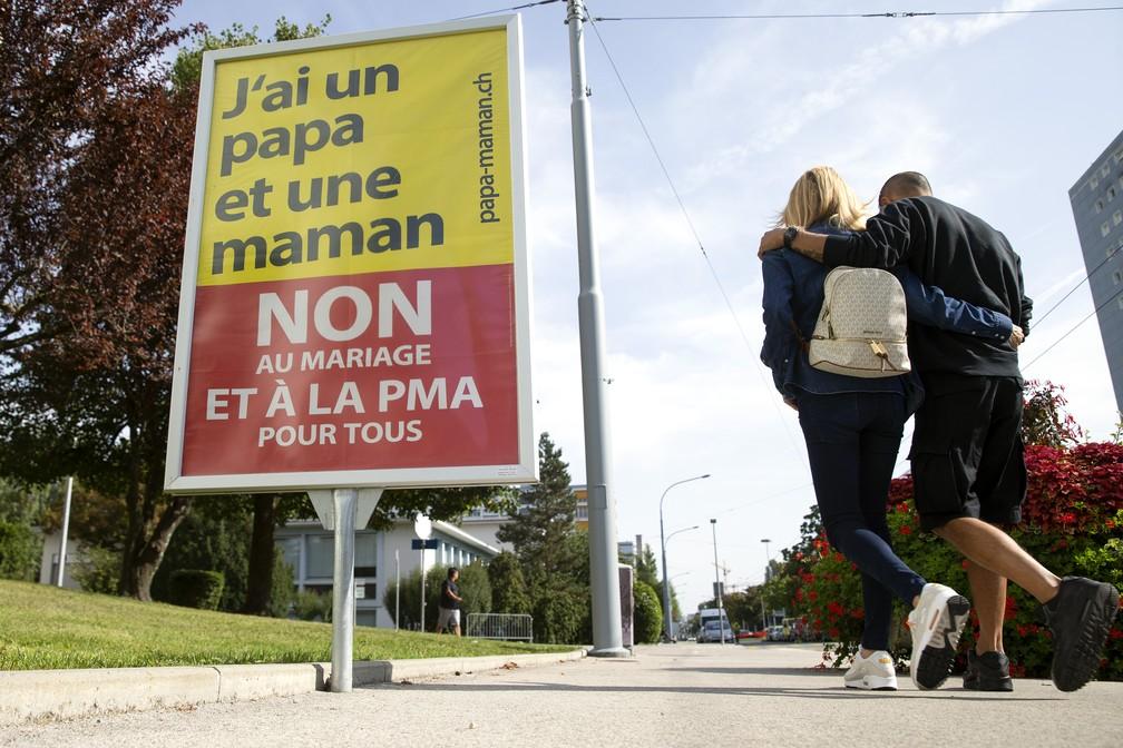 Placa contra o casamento igualitário diz, em francês, que 'eu tenho um papai e uma mamãe; não ao casamento e à reproduçõ assistida para todos' em Genebra, na Suíça, no sábado (25). — Foto: Salvatore Di Nolfi/Keystone via AP