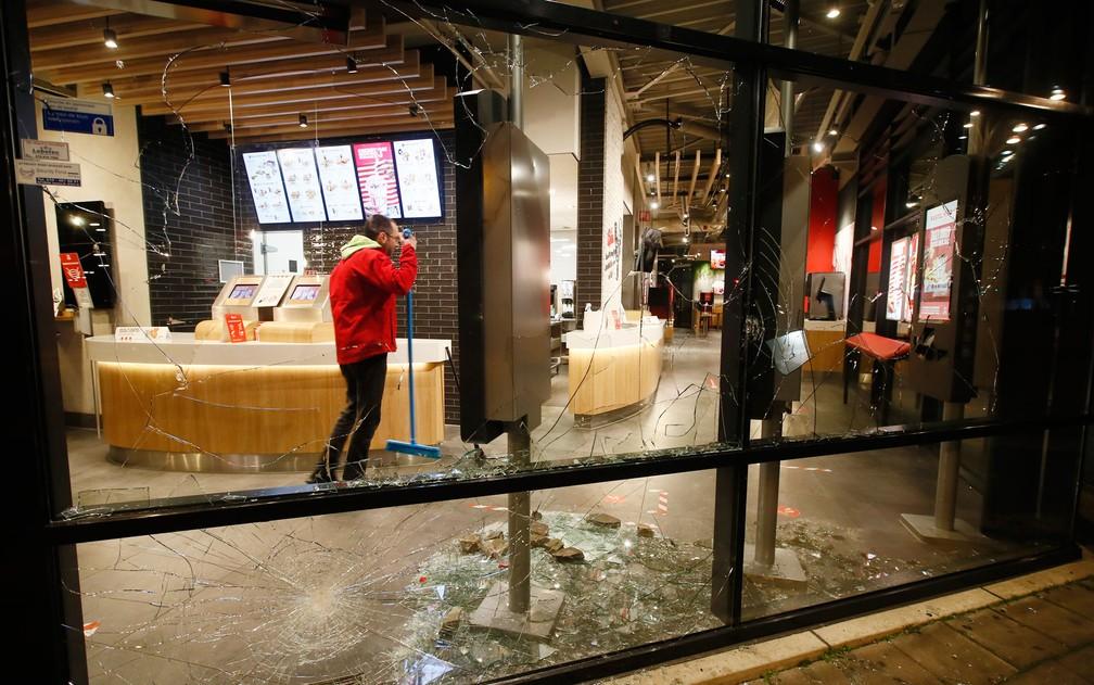 Homem limpa restaurante de fast food com janelas quebradas durante protesto contra toque de recolher em Roterdã, na Holanda, na segunda-feira (25) — Foto: AP Photo/Peter Dejong