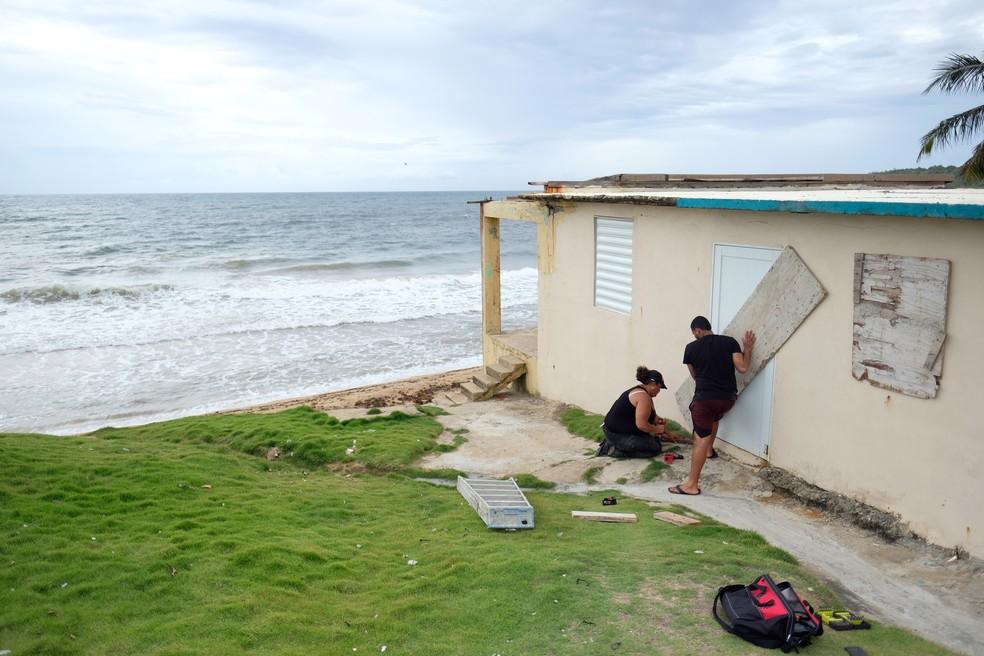 Casal reforça a proteção da porta de uma casa perto do mar em Porto Rico — Foto: Ricardo Arduengo/Reuters