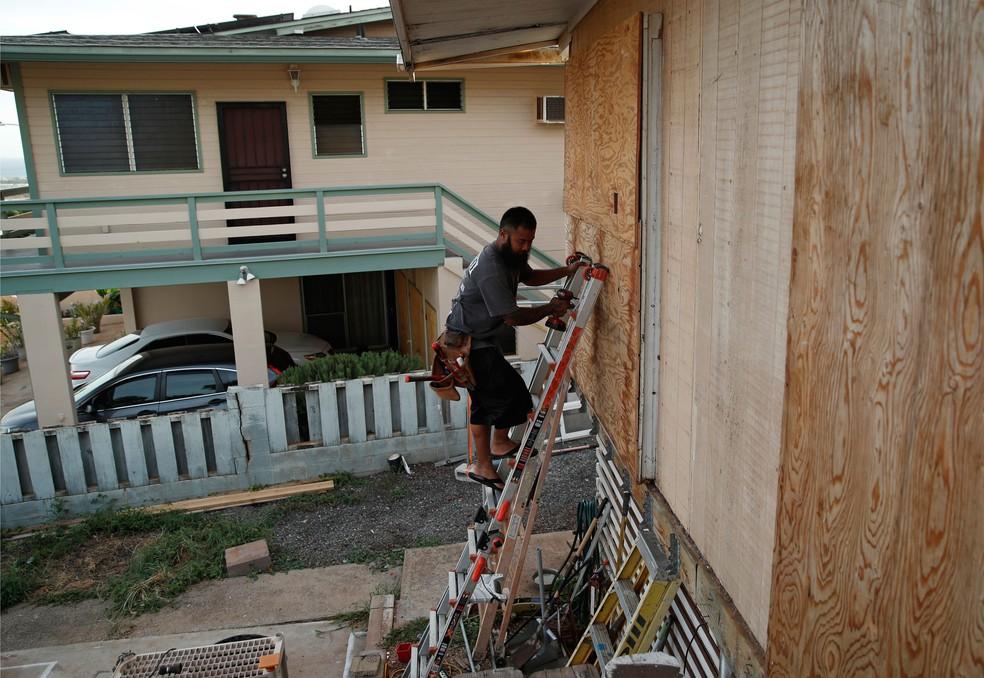 Morador protege janela com madeira em Kapolei, no Havaí, na quarta-feira (22), na preparação para a chegada do furacão Lane  (Foto: John Locher/AP)