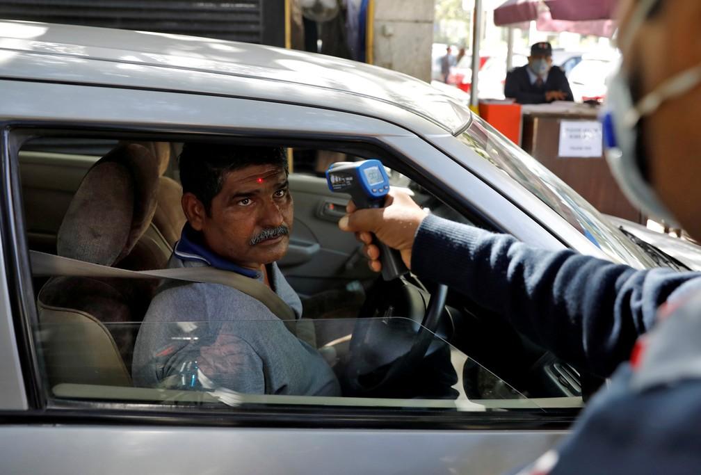 9 de março - Um homem tem sua temperatura medida por um segurança com um um termômetro infravermelho durante sua chegada a um prédio de escritórios em Nova Délhi, na Índia — Foto: Adnan Abidi/Reuters