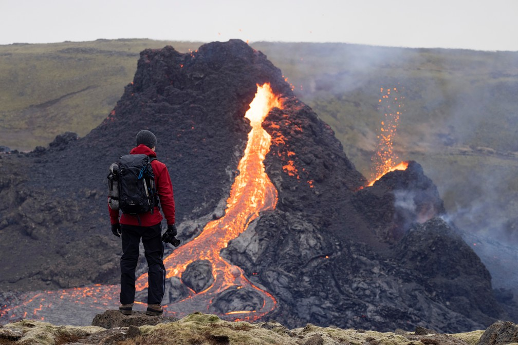 Pessoa em frente ao local do vulcão na Península de Reykjanes no domingo (21), na Islândia, após a erupção de sexta-feira (19) — Foto: Cat Gundry-Beck/Reuters