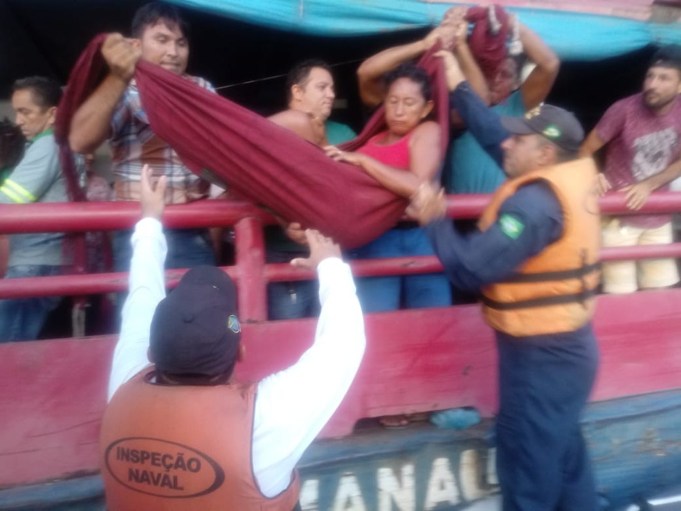 Uma rede foi utilizada para facilitar a remoção de Lenice Ferreira da balsa para a lancha da Marinha — Foto: CFS/Divulgação